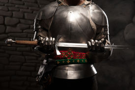 stock photo of sword  - Closeup portrait of medieval knight in armor holding a sword in dark stone wall background - JPG