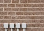stock photo of cinder block  - Cement cinder block wall with electrical boxes - JPG