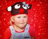 pic of rudolph  - Closeup portrait of a little baby girl wearing funny Rudolph hat over red snowy background - JPG