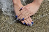 picture of nail paint  - Finger nail treatment hands with painted fingernails at sand in water - JPG