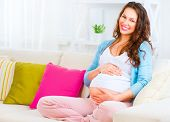 stock photo of expectations  - Pregnant Happy smiling Woman sitting on a sofa and caressing her belly - JPG