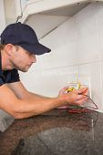 stock photo of  multimeter  - Electrician metering voltage with digital multimeter in the kitchen - JPG