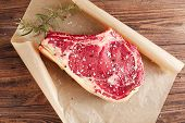 pic of ribs  - raw beef Rib steak with bone on wooden board and table - JPG