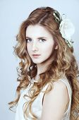picture of shy woman  - Tender young woman with long curtly blond hair and an orchid flower in her hair - JPG