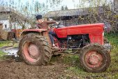 foto of plow  - Senior farmer on an old red tractor plowing his garden in the backyard  - JPG