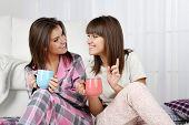 pic of pajamas  - Beautiful girls twins in pajamas drinking tea at home - JPG