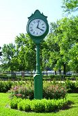 pic of tick tock  - Scenic Outdoor clock in the park surrounded by flowers - JPG