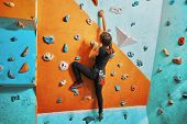stock photo of climbing wall  - Young woman climbing up on practice wall in gym rear view - JPG