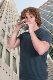 stock photo of tin man  - Young man using tin can phone technology - JPG