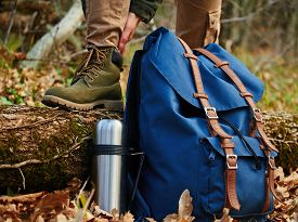 stock photo of thermos  - Female hiker wears boots outdoors in autumn forest near thermos and backpack - JPG