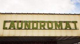 stock photo of laundromat  - Old green Laundromat sign against blue sky and clouds - JPG