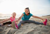 image of mother baby nature  - Healthy mother and baby girl stretching on beach in the evening - JPG
