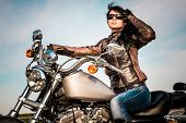 picture of motorcycle  - Biker girl in a leather jacket on a motorcycle looking at the sunset - JPG