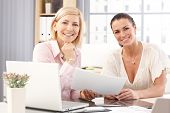 pic of blonde  - Happy casual blonde and brunette businesswomen at office working in front of laptop computer - JPG