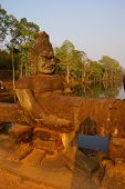 image of demons  - Stone Asura demons hold the naga serpent king Vasuki on the bridge entrance to Angkor Thom Cambodia - JPG