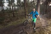 stock photo of dirt-bike  - Young man standing in the forest posing proudly with his ATB bike - JPG