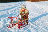 pic of jumpsuits  - Little boy in warm jumpsuit pushes sled near forest at winter sunny day  - JPG