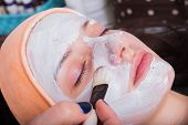 image of rubber mask  - Spa therapy for young woman receiving facial mask at beauty salon - JPG