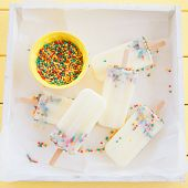 stock photo of popsicle  - Homemade frozen vanilla popsicles with colorful sprinkles - JPG