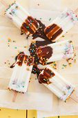 foto of popsicle  - Homemade frozen vanilla popsicles with colorful sprinkles - JPG