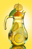 foto of pitcher  - Misted lemonade pitcher with lemon slices and ice cubes decorated with quarter lemon cap on yellow - JPG