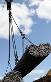 stock photo of reinforcing  - crane lifts and moves a pack with metal reinforcement against the sky with clouds - JPG