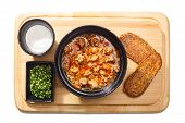 foto of condiment  - Savory soup with meat on a wooden plate served with sour green condiment and whole grain bread - JPG