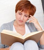 pic of only mature adults  - Adult woman reading book at sofa - JPG