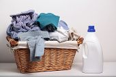 picture of dirty-laundry  - Dirty clothes in the laundry basket and a bottle of detergent - JPG