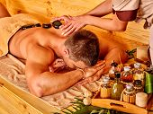 foto of stone-therapy  - Man getting stone therapy massage in bamboo spa - JPG