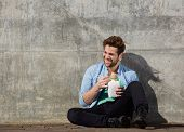 stock photo of chinese food  - Portrait of a cheerful young man eating chinese take away food with chopsticks - JPG