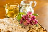 stock photo of wildflower  - Sweet Japanese plum wine with fruit in glass photographed with beautiful pink wildflowers - JPG