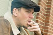 stock photo of newsboy  - Cool guy in aviator jacket and newsie cap relaxes against a glass wall and enjoys his cigarette - JPG