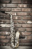 pic of lonely  - Lone old saxophone leans against brick wall outside abandoned jazz club - JPG