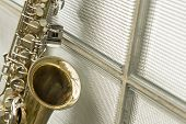 stock photo of saxophones  - Lone old saxophone leans against brick wall outside abandoned jazz club  - JPG