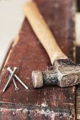 image of work bench  - Old and worn contracting hammer and three nails on a distressed work bench - JPG