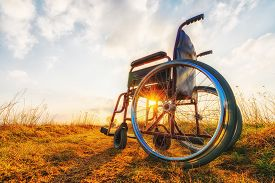 stock photo of wheelchair  - Empty wheelchair on the meadow at sunset - JPG