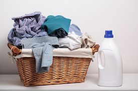 stock photo of detergent  - Dirty clothes in the laundry basket and a bottle of detergent - JPG