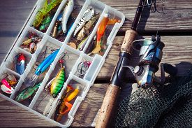 foto of fishing bobber  - Fishing Lures in tackle boxes with spinning rod and net on wooden pier - JPG
