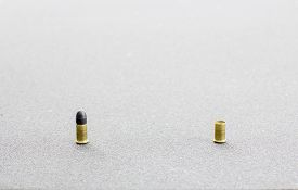 stock photo of cartridge  - Small caliber cartridge and a cartridge case in a rough grey background - JPG