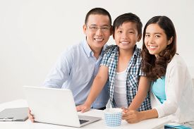 foto of schoolboys  - Portrait of schoolboy and his parents sitting at the laptop - JPG