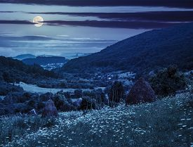 foto of haystacks  - haystack on a green agricultural meadow in the mountains at night in full moon light - JPG