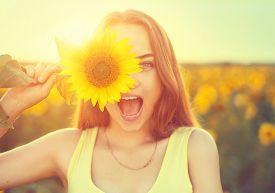 pic of glow  - Beauty joyful teenage girl with sunflower enjoying nature and laughing on summer sunflower field - JPG