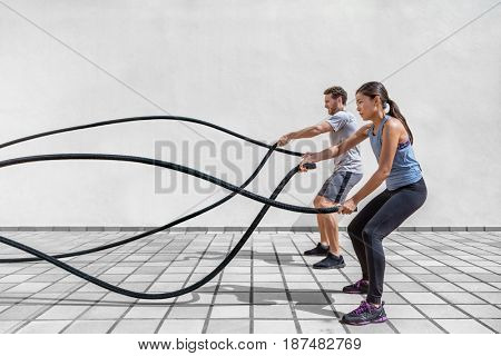 poster of Fitness people exercising with battle ropes at gym. Woman and man couple training together doing bat