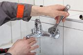 stock photo of plumber  - Plumber hands fixing water tap with spanner - JPG