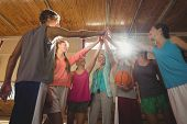Female coach and high school kids giving high five to each other in basketball court poster