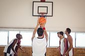 Basketball player about to take a penalty shot while playing basketball in the court poster