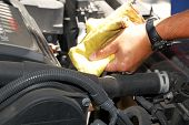 stock photo of partially clothed  - Shot of an automobile oil change with partial hand - JPG