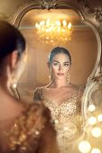 Beauty glamour lady looking in the mirror. Beautiful gorgeous woman in beautiful evening dress in Lu poster