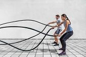 Fitness people exercising with battle ropes at gym. Woman and man couple training together doing bat poster